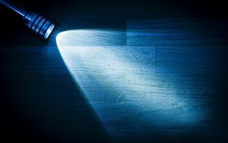 Flashlight shining a beam of light in darkness